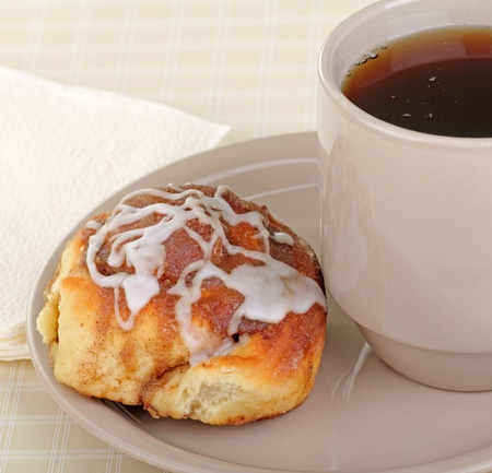 Cinnamon roll and cup of coffee on a plate Stock Photo - 17596851