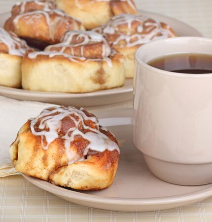 Cinnamon roll and cup of coffee on a plate with plate of rolls in background Stock Photo - 17596857