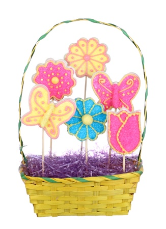 Easter sugar cookies shaped like flowers and butterflies in a basket isolated on wlhite photo