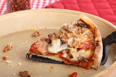 Slice of deep dish pizza in a pizza pan Stock Photo - 17717011