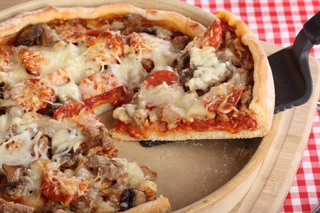 Slice of deep dish sausage and pepperoni pizza in a pizza pan Stock Photo - 17717003