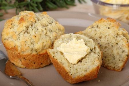 Herb muffins on a plate with one cut in half with butter Stock Photo - 17717001