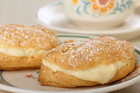 powdered sugar: Eclairs with powdered sugar on top on a plate Stock Photo