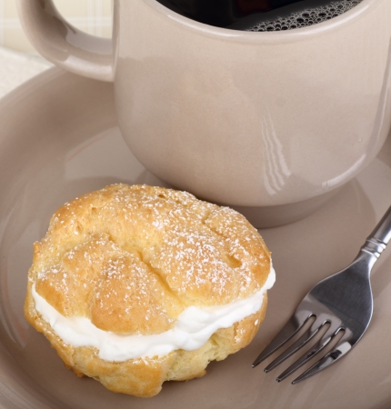 Cream puff and cup of coffee on a plate