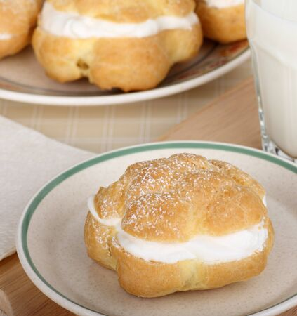 Cream puff with powdered sugar on top on a plate