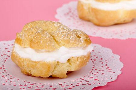 Cream puff pastry on a pink table Stock Photo