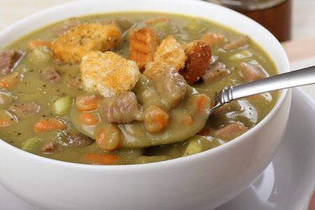 Spoonful of ham and pea soup with croutons