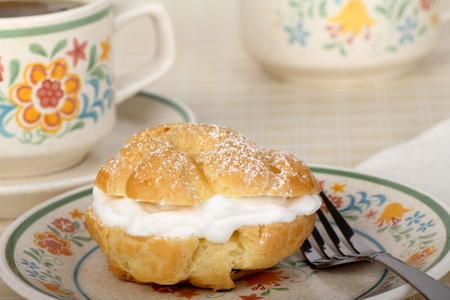 Cream puff with powdered sugar and coffee in background