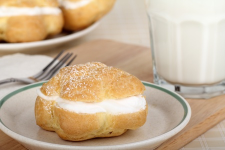 Cream puff on a plate with a glass of milk