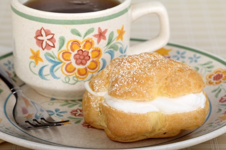 Cream puff on a plate with cup of coffee photo