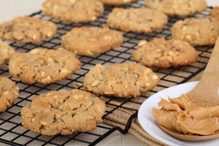 Peanut butter cookies on a cooling rack with a spoon of peanut butter on side