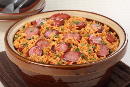 Kielbasa sausage with rice sprinkled with parsley in a pot