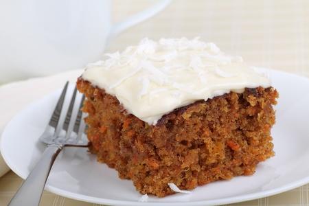 Stukje wortel taart bestrooid met kokos op een bord