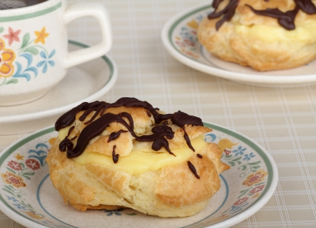 eclair: Eclair pastry with chocolate on a plate Stock Photo