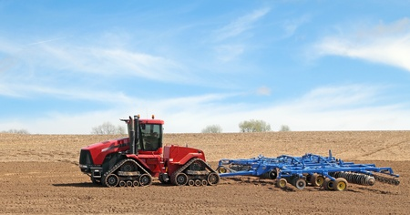 Red tractor pulling a plow in a farm field