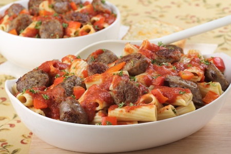 Sliced bratwurst and rigatoni pasta with tomato sauce photo