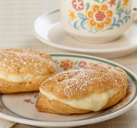 Two cream filled eclairs with powdered sugar on a plate Stock Photo