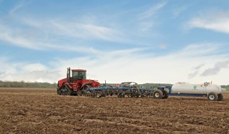 ammonia: Red tractor que tira del arado y el tanque de amon�aco anhidro Foto de archivo