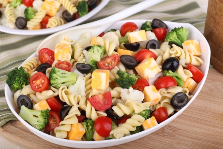 broccoli salad: Pasta salad with tomato, broccoli, black olives, cauliflower and cheese in a bowl