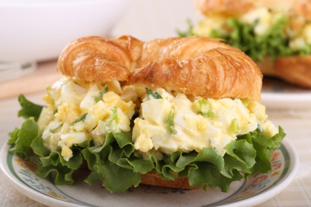 Closeup of an egg salad sandwich on a croissant bun