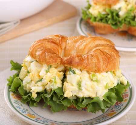 Egg salad and lettuce on a croissant roll