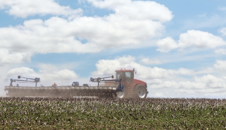 Red tractor pulling a planter in a farm field