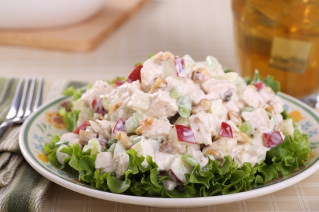Chicken salad with apple pieces and nuts on top of lettuce