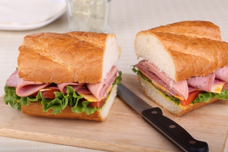 Sandwich con embutidos queso lechuga y tomate en pan franc�s Foto de archivo - 21600082