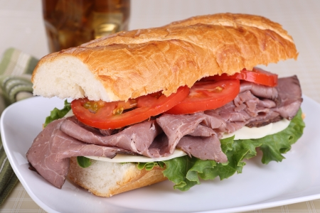 Sandwich with roast beef cheese lettuce and tomato on french bread on a plate Stock Photo