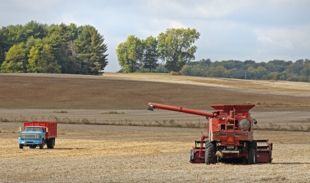 Combine and truck in a harvested soybean field