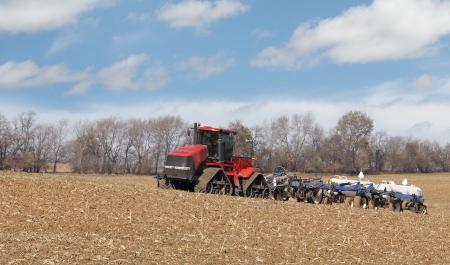 amoniaco: Red tractor tirando de tanques de amoníaco anhidro en un campo agrícola Foto de archivo