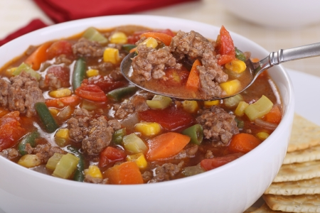 ground beef: Vegetable soup with hamburger meat on a spoon