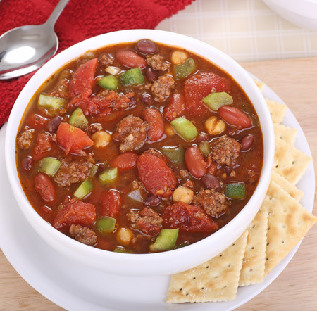 ground beef: Chili with beans, hamburger, tomatoes and peppers in a white bowl