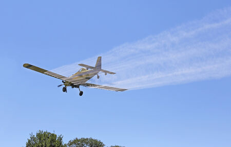 Airplane spraying pesticides over a farm field Stock Photo