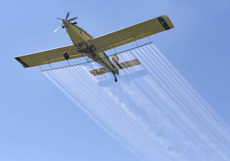 Airplane spraying insecticides over a farm field