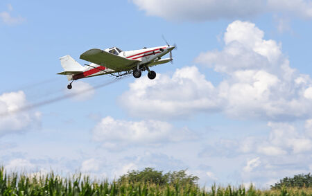 Airplane spraying pesticides over a corn field photo