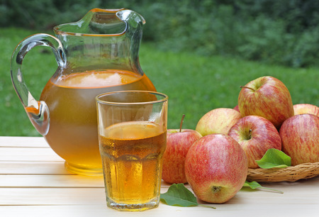 Glass of apple juice with apples and pitcher in background