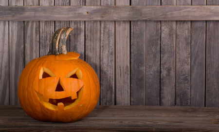 Smiling carved pumpkin on a wood floor with fence in background