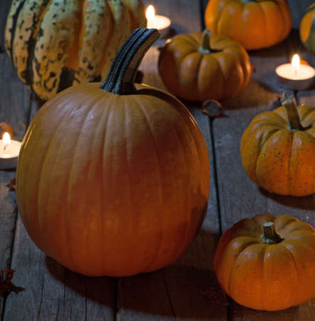 Various pumpkins and gourds on a wood floor lit by candles Stock Photo