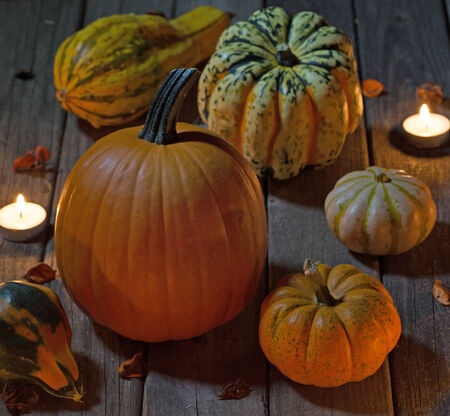 Various pumpkins and gourds lit by candles on a wood floor