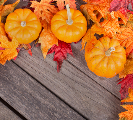 Pumpkins and fall leaves on a wood deck Stock Photo
