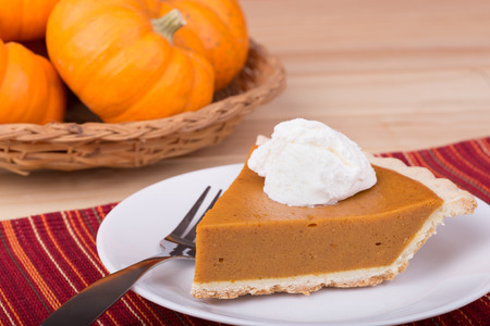 Slice of pumpkin pie with whipped cream and a basket of pumpkins in background photo
