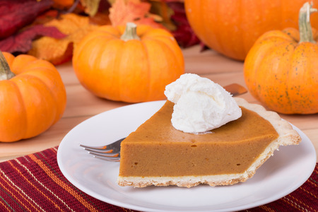 Slice of pumpkin pie with whipped topping and pumpkins in background Stock Photo