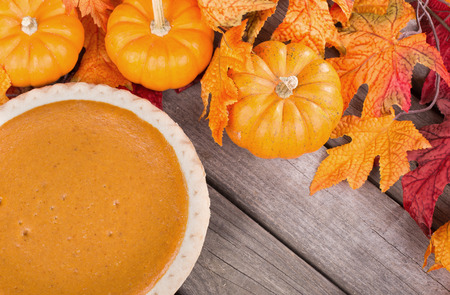 Pumpkin pie with pumpkins and leaves on a wood background