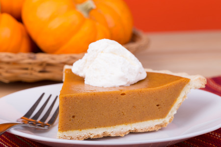 Closeup of pumpkin pie slice with pumpkins in background