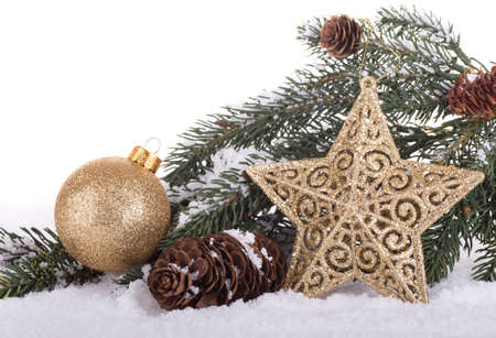 Holiday star and ball with evergreen branch and pinecone on snow and white background