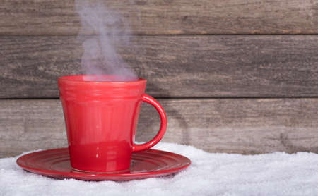 coffee cups: Red steaming cup of coffee on snow with wooden background