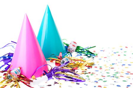 Two colorful birthday party hats with noisemakers and confetti on a white background Foto de archivo