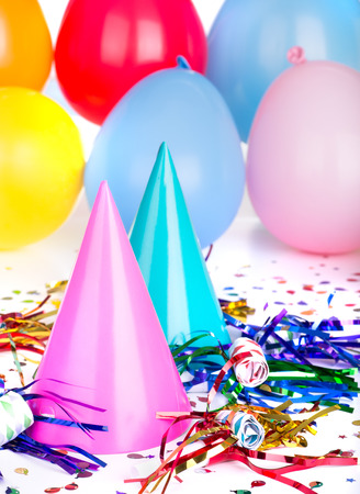 festive occasions: Two birthday hats with noisemakers and confetti and balloons in background Stock Photo