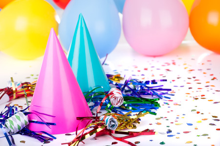 Birthday party decorations of hats, noisemakers, confetti and balloons Banco de Imagens